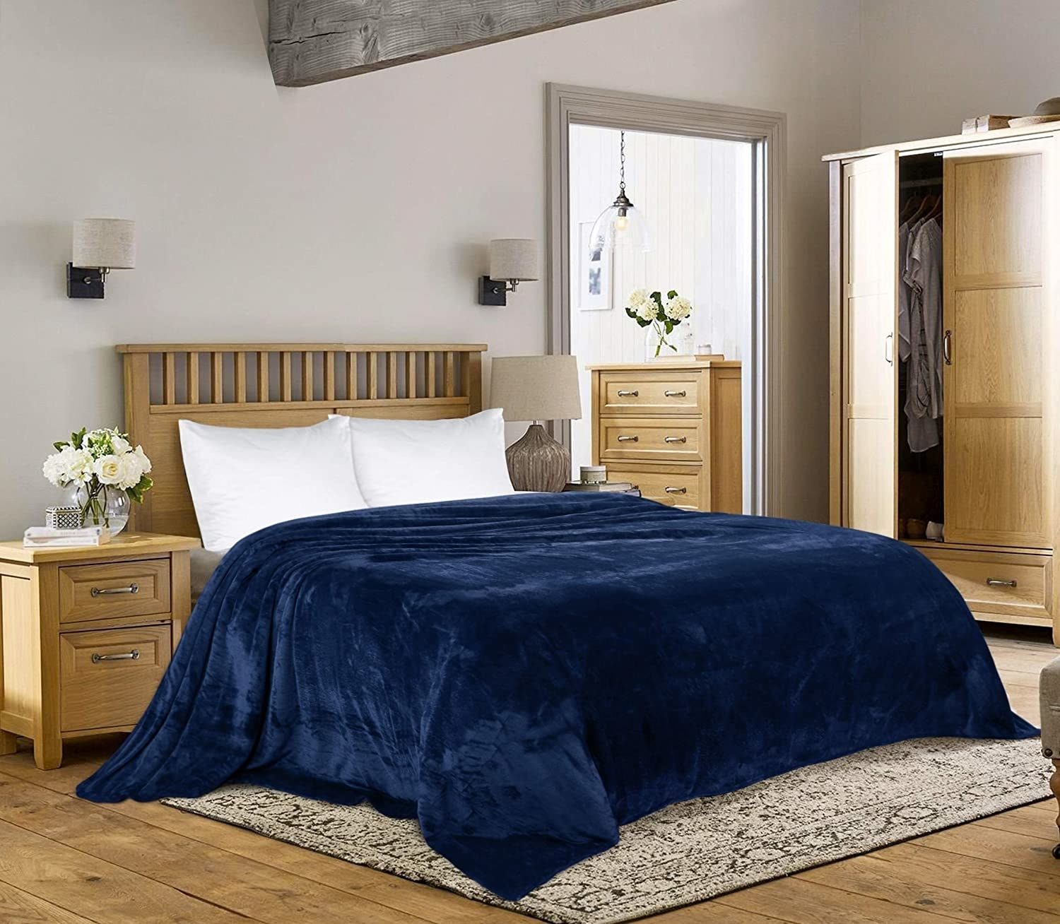 the navy blue fleece blanket spread over a bed