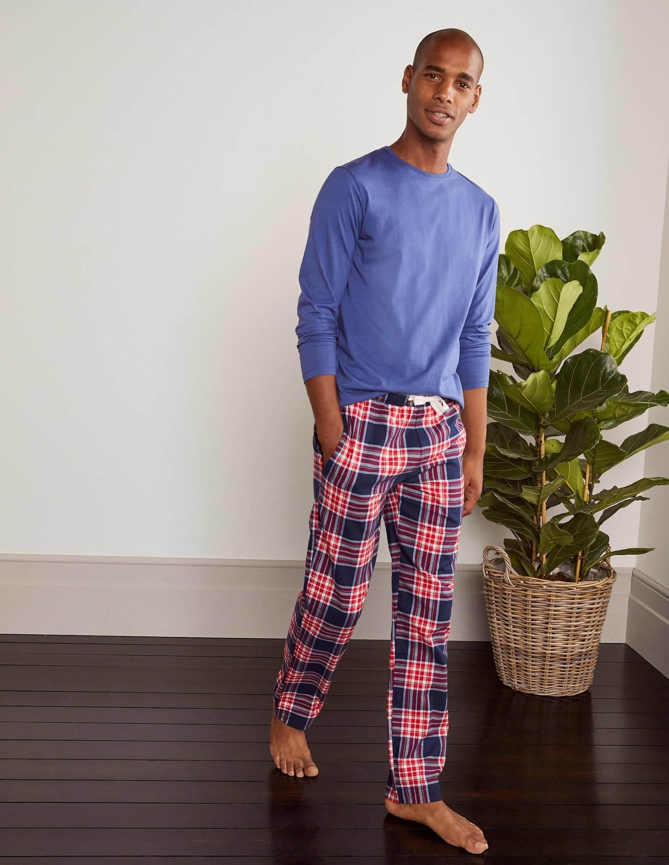 Model wearing the full-length pajama bottoms with an elastic waist in red and blue plaid