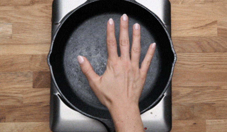 A hand over a pre-heating cast iron pan.