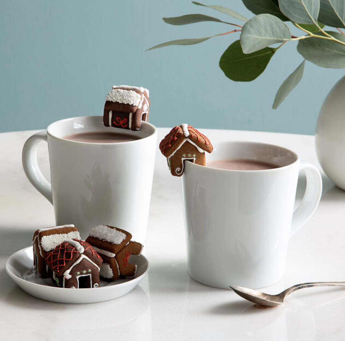 mugs that have little gingerbread houses perched on the lip of them