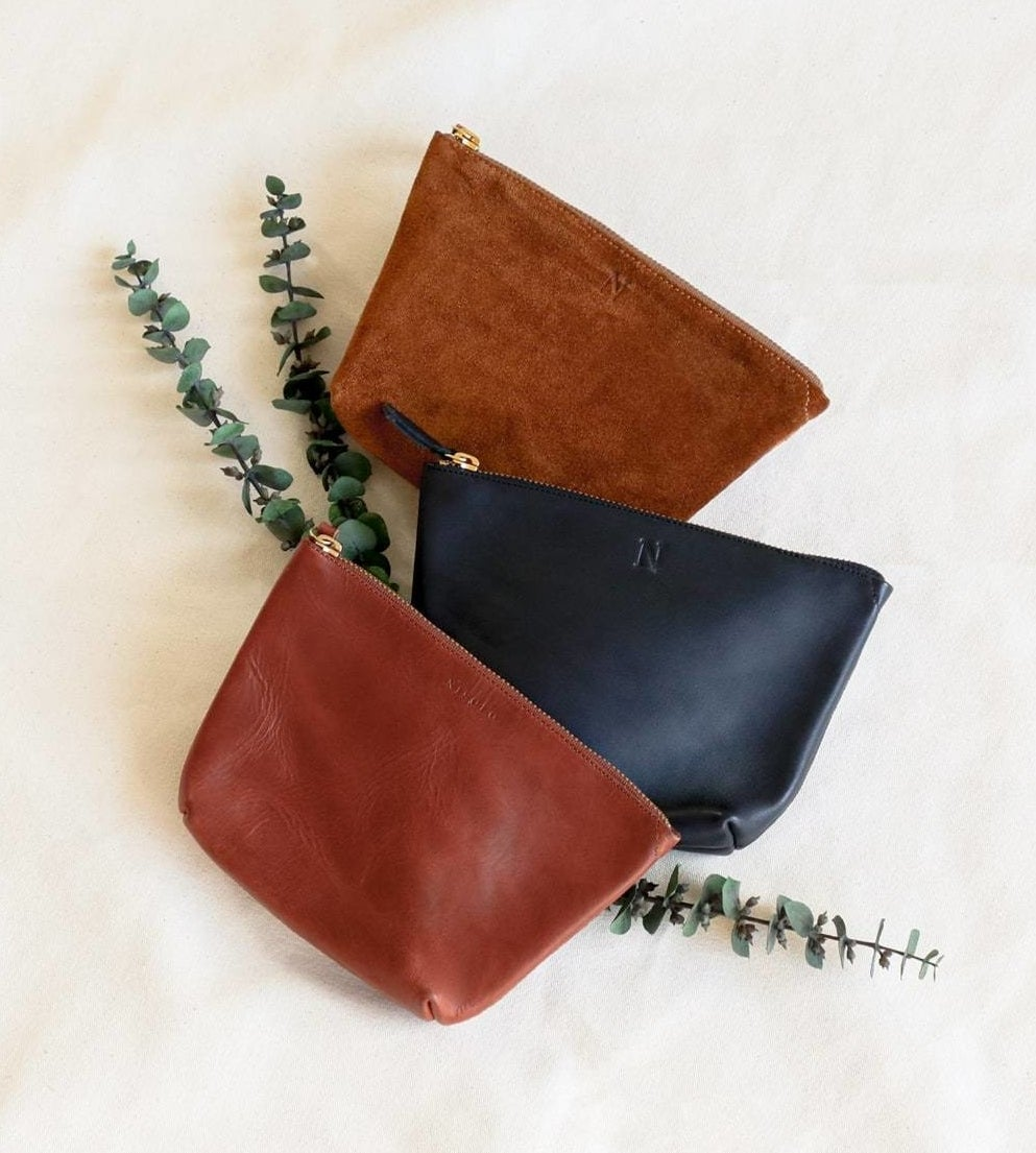 The brown and black leather pouches and the suede brown with zippers on the top