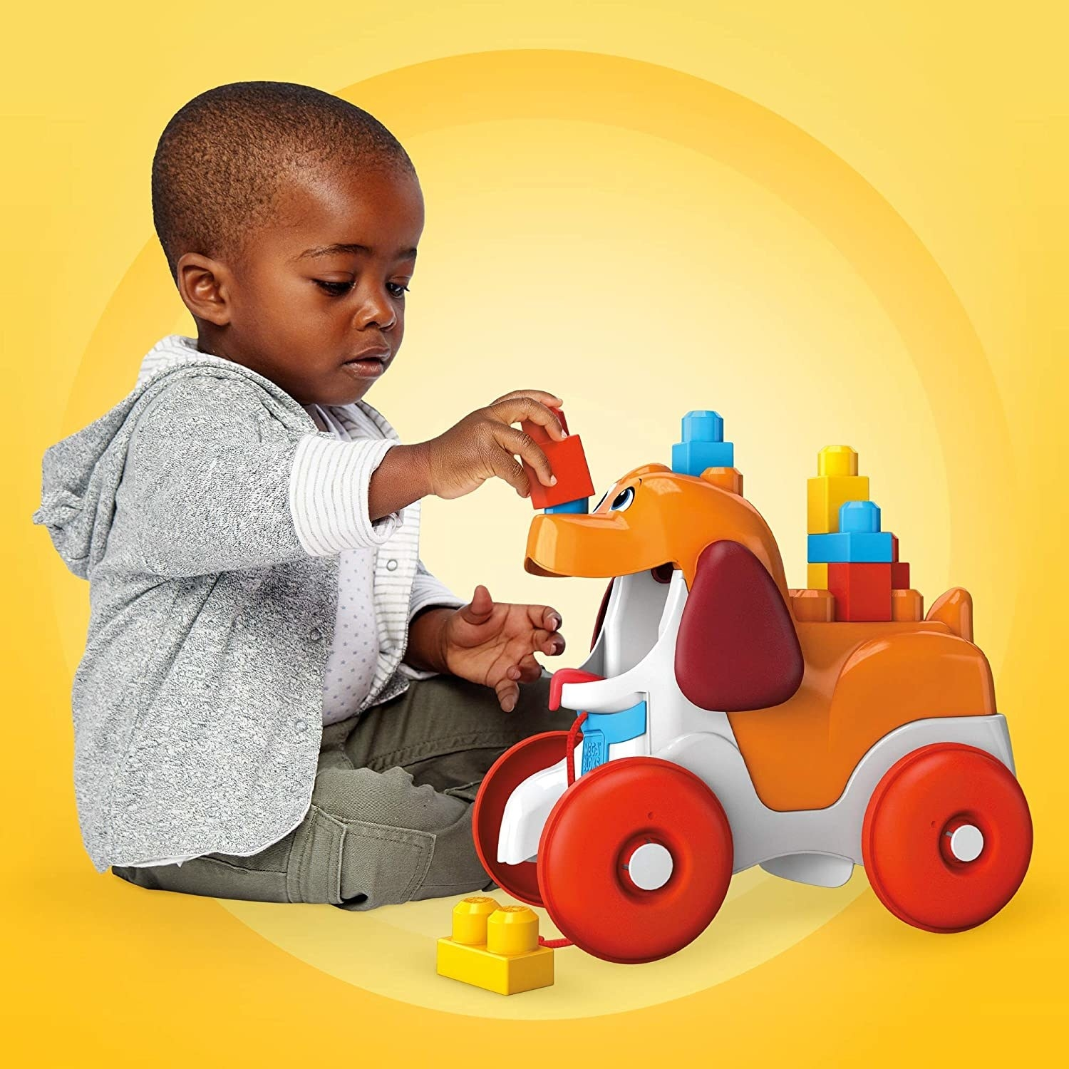 Child model playing with bright plastic dog toy with red wheels