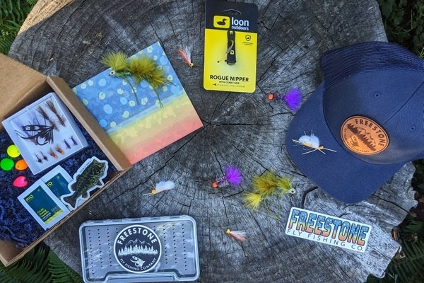 an unpacked box featuring fishing flies, a hat, and other fishing gear