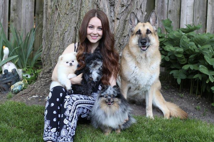 Vanessa sitting in front of a tree with four dogs