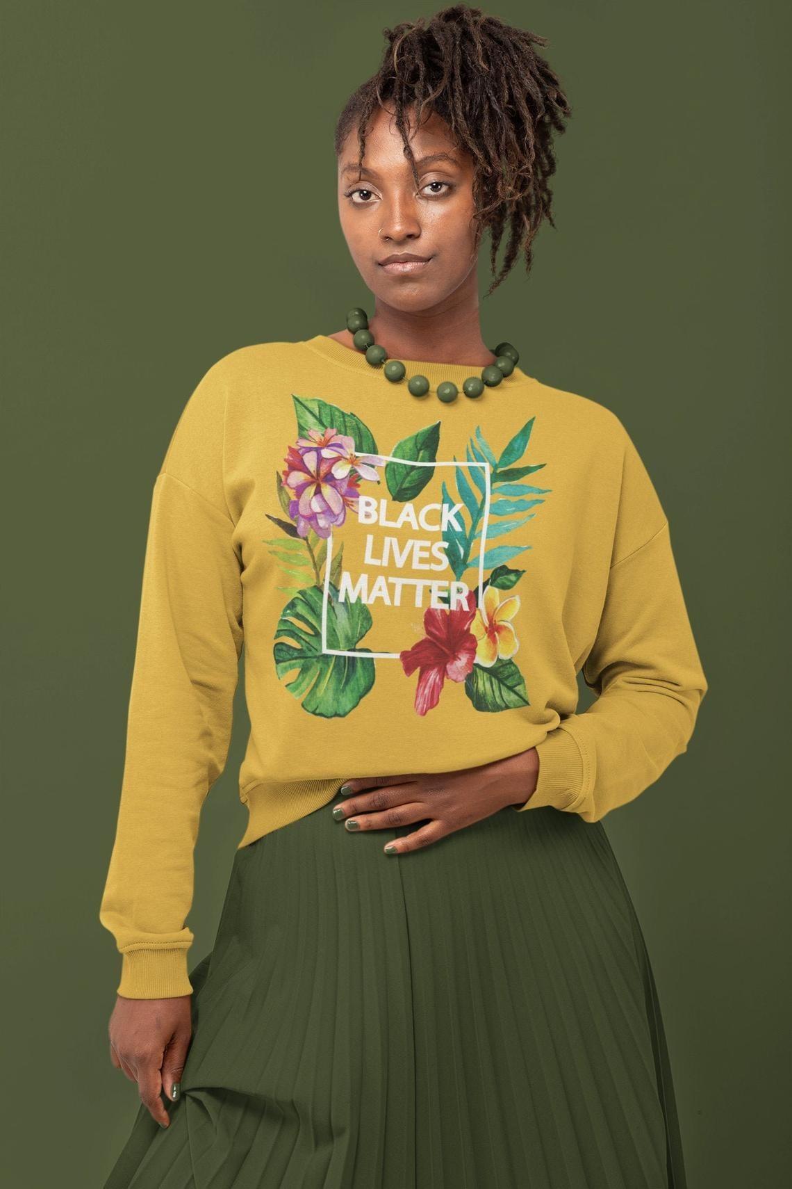 "Yellow sweatshirt with botanical pattern framed around words ""Black Lives Matter"""