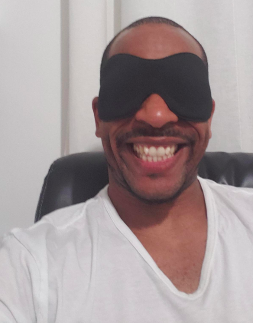 A reviewer wearing the sleep mask