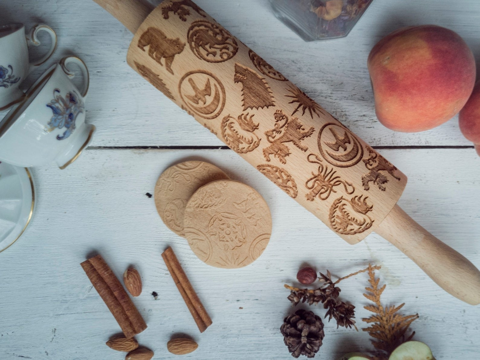 rolling pin embossed with Game of Thrones insignias next to two patterned cookies