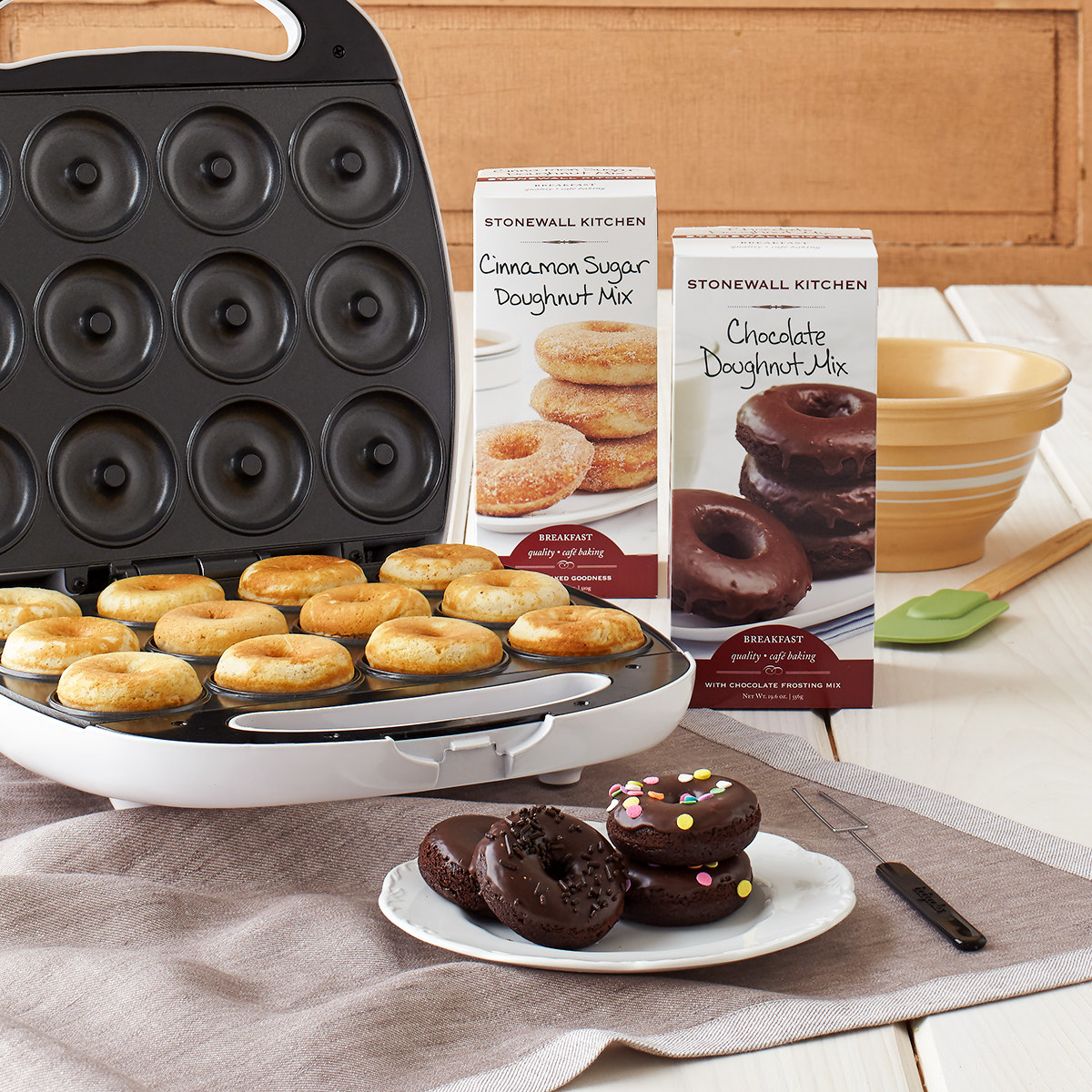 Mini doughnuts cooked in a doughnut maker alongside the two doughnut mixes