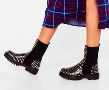A person wears a pair of boots with studs
