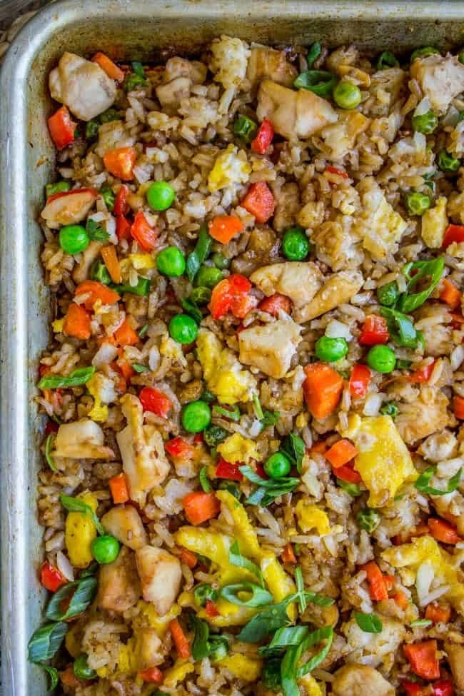 A sheet pan topped with chicken fried rice with veggies.