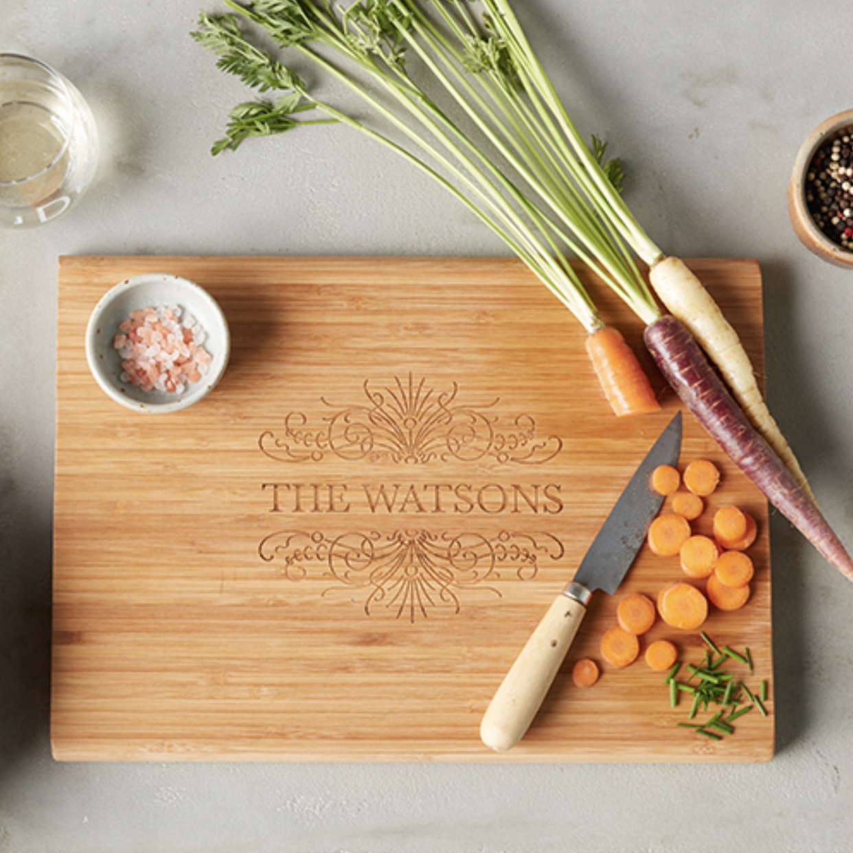 "The brown wood square cutting board with the words ""The Watsons"" and a design above and below the name"