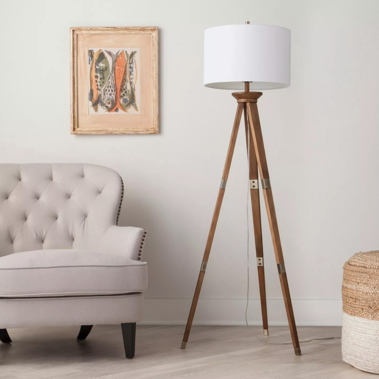 The tripod floor lamp with oak wood legs and a white shade