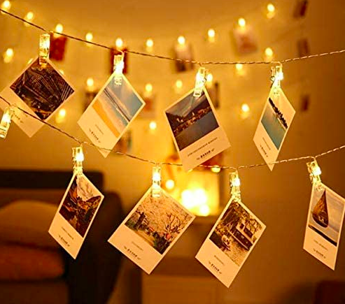 Tiny photo notecards hanging on lit string lights with slim clips