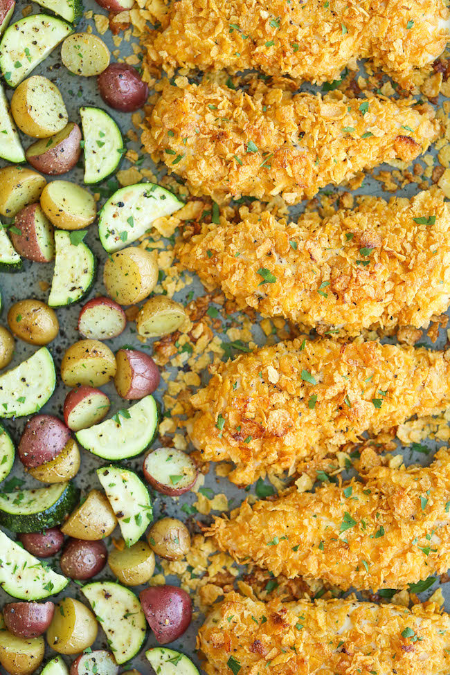 Crispy chicken tenders on a sheet pan with diced tomatoes and zucchini.