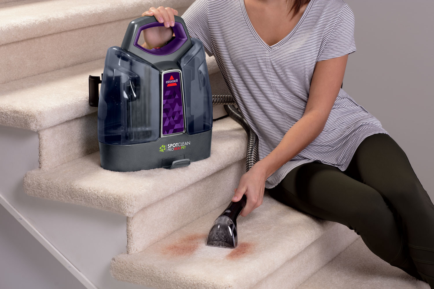 person using a bissell spot cleaner to clean up a carpet stain