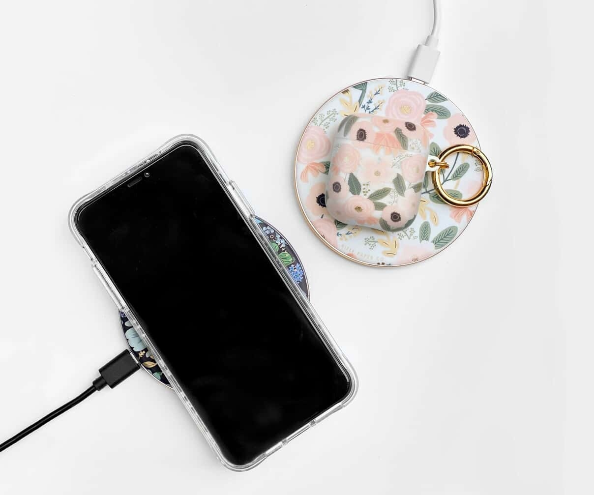 Two circular chargers in floral prints with a phone on one and AirPods on the other