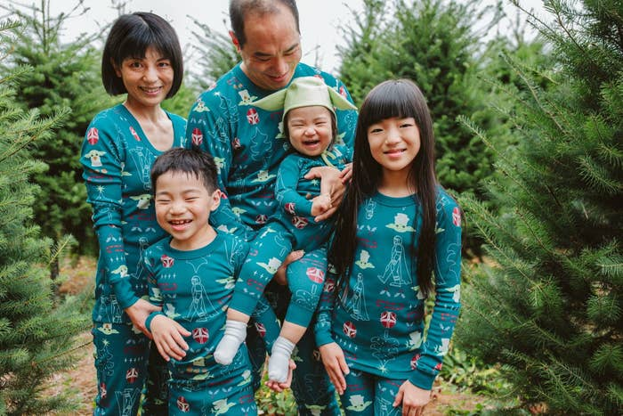 an entire family in green pajamas with icons of baby yoda and the mandalorian on it