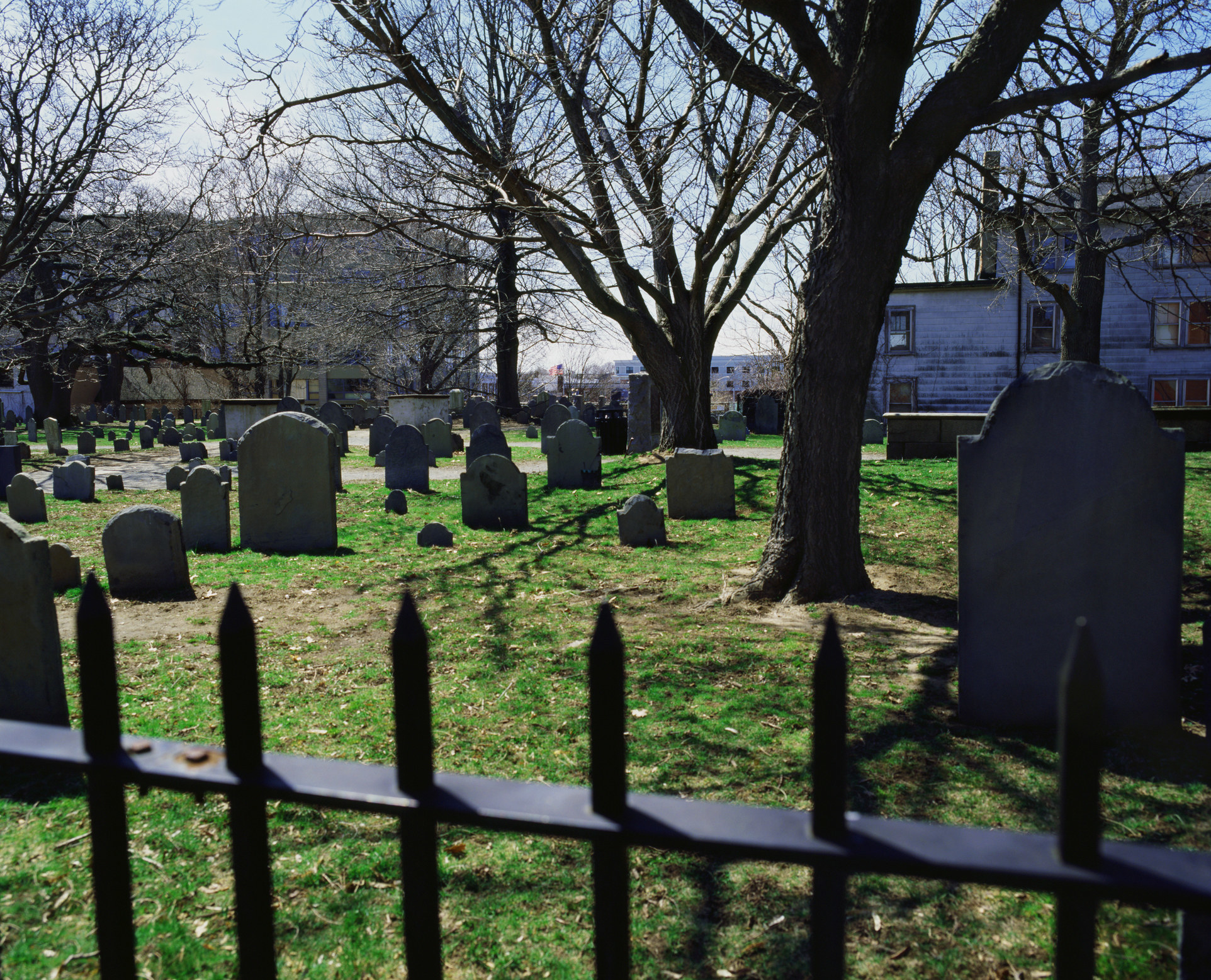 a fenced off grassy field with gravestones and trees