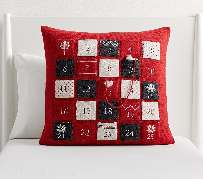 a red pillow with little decorative pockets on it labeled 1 through 25