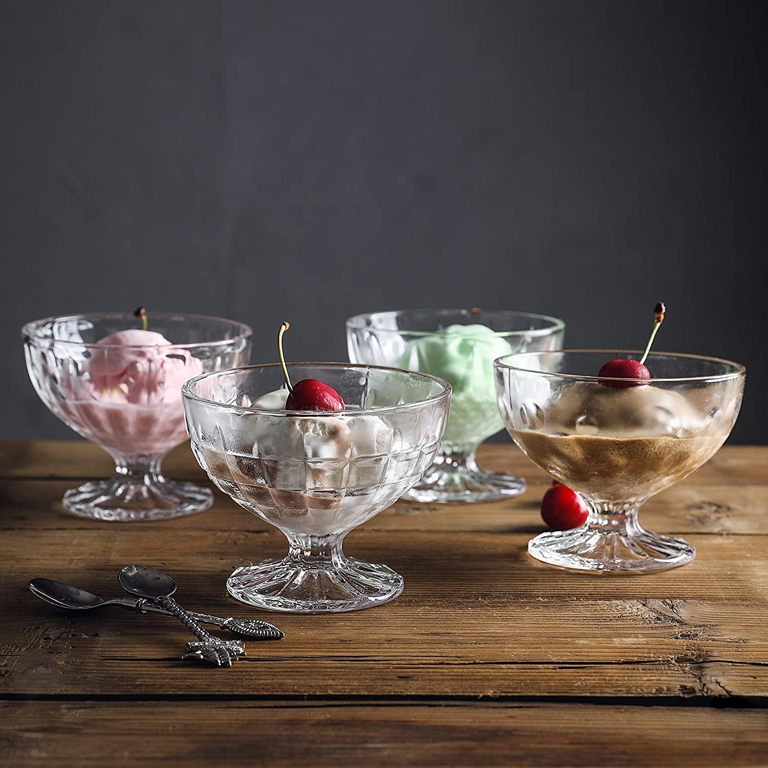 Four small glass ice cream cups with small stems that have different patterns etched into their glass