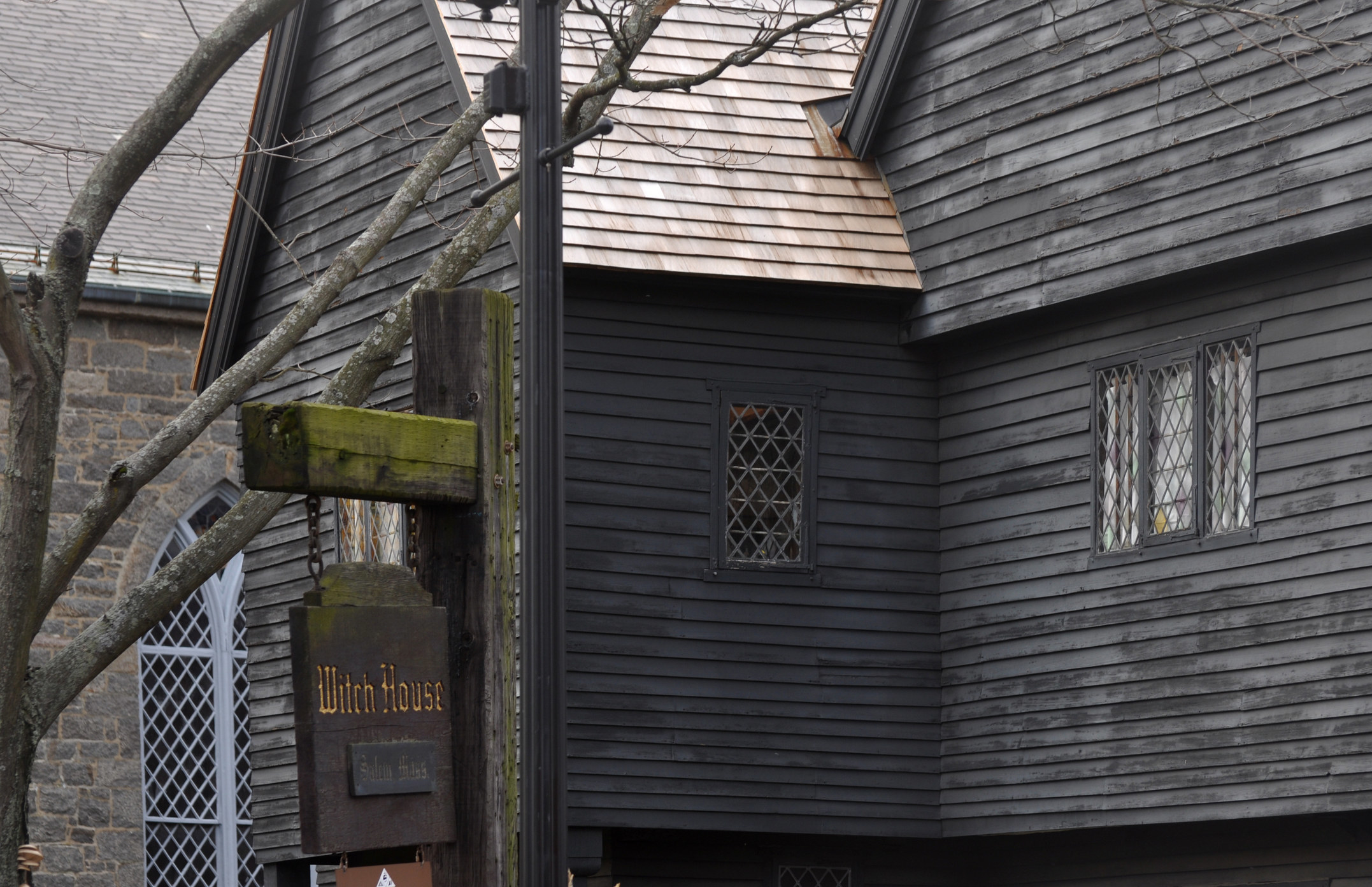 "old black weatherboard historical house in Salem with sign reading ""Witch House"""