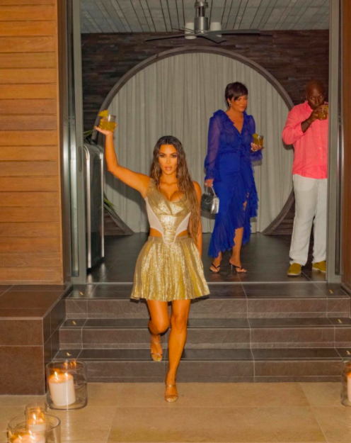 Kim raising a cocktail in the air as she walks down steps during her b-day party as her mother Kris Jenner and Kris' boyfriend Corey Gamble look on