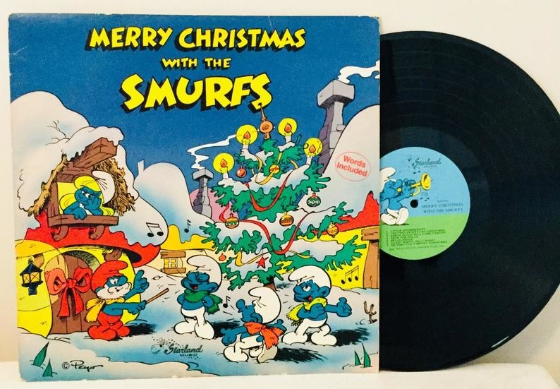 The cover Merry Christmas with the Smurfs album which features Papa Smurf leading a chorus of three singing Smurfs and Smurfette looking from the window