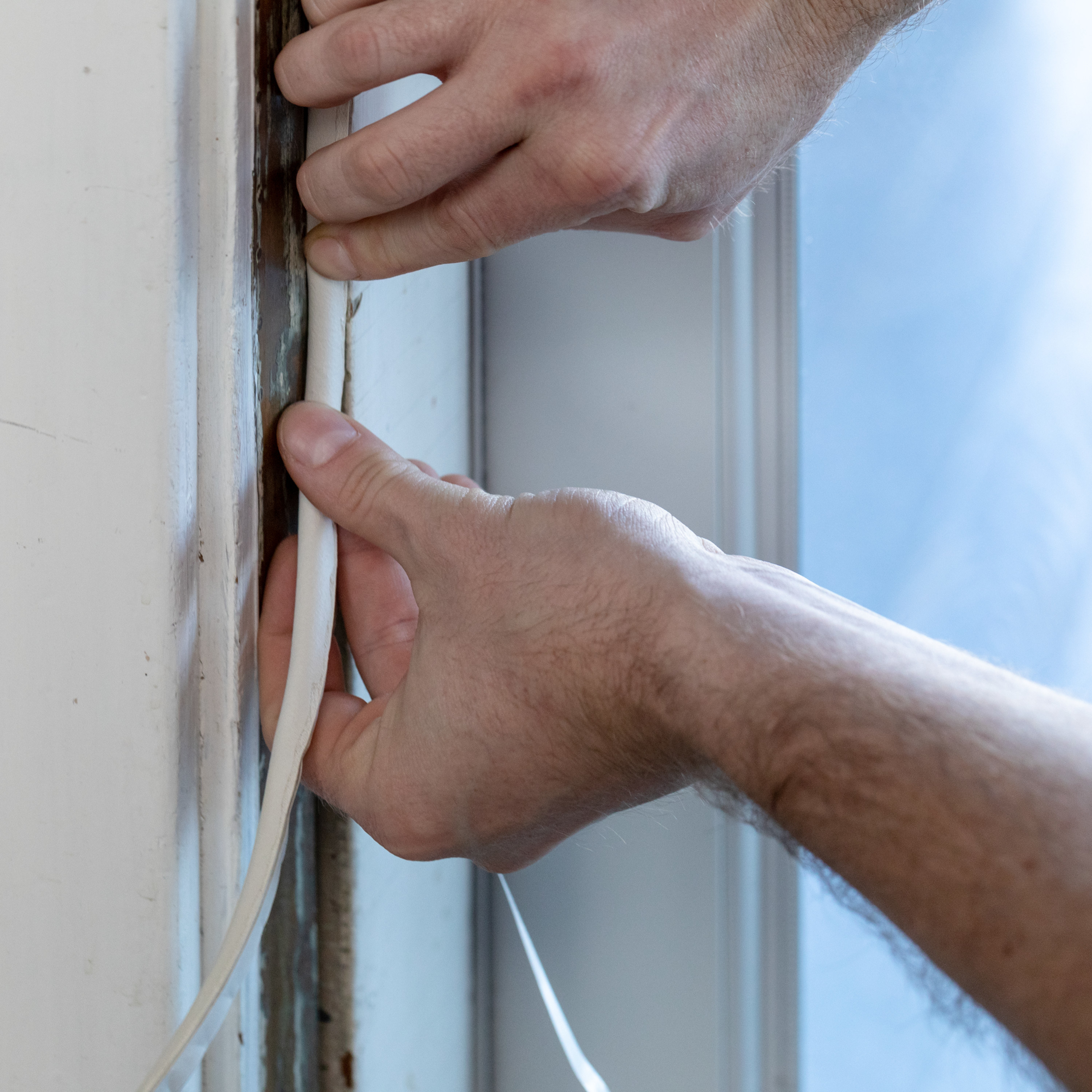 person applying a weather stripping seal onto a door frame