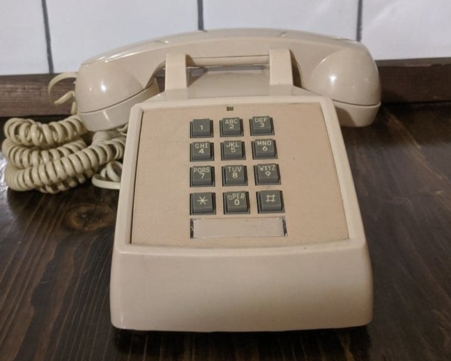 A beige landline phone with push-down gray buttons