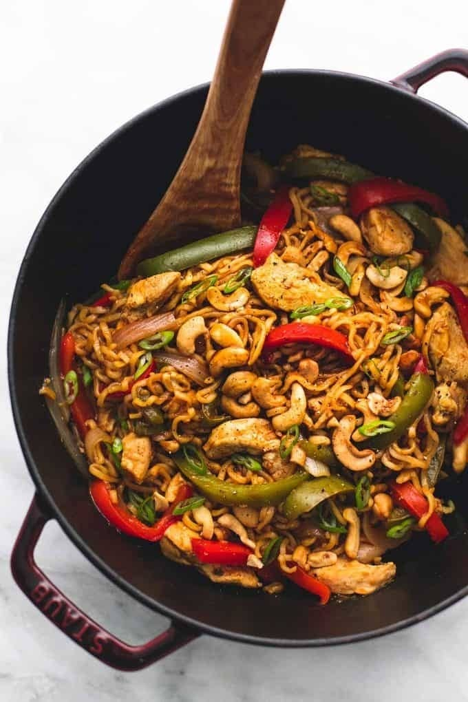 A skillet of ramen noodles stir-fried with chicken, cashews, and peppers.
