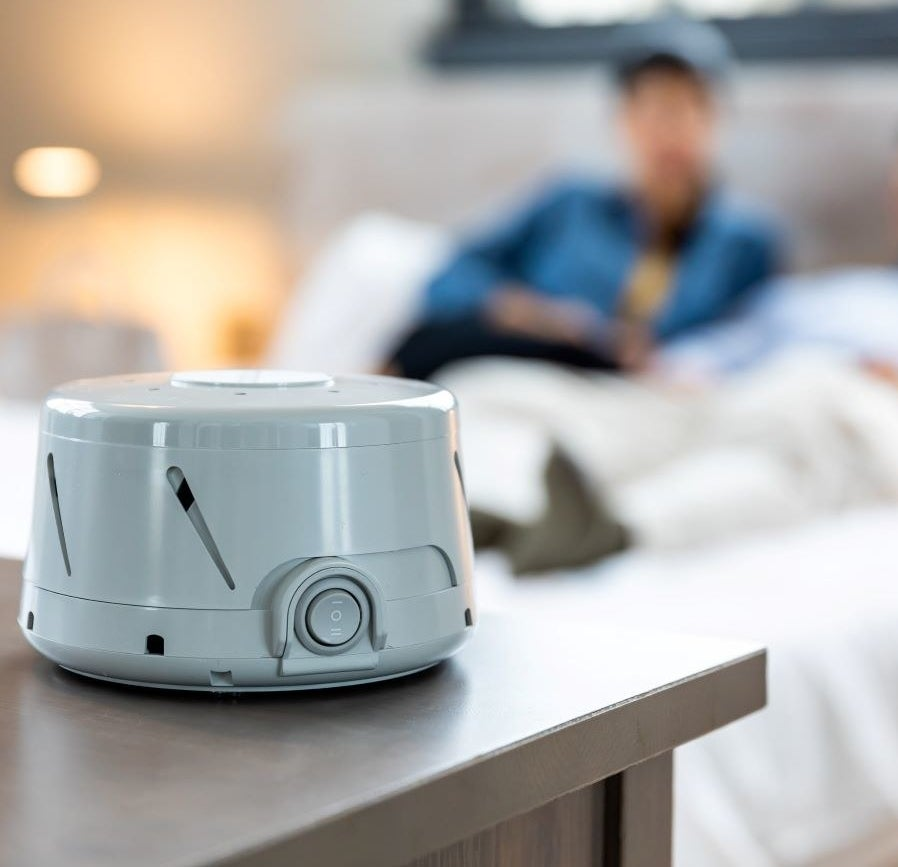 gray white noise machine sitting on a dresser in a bedroom