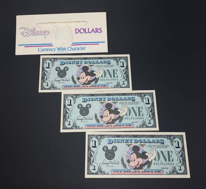 An envelope with Disney Dollars written on it and three $1 Disney Dollars that features Mickey waving on them