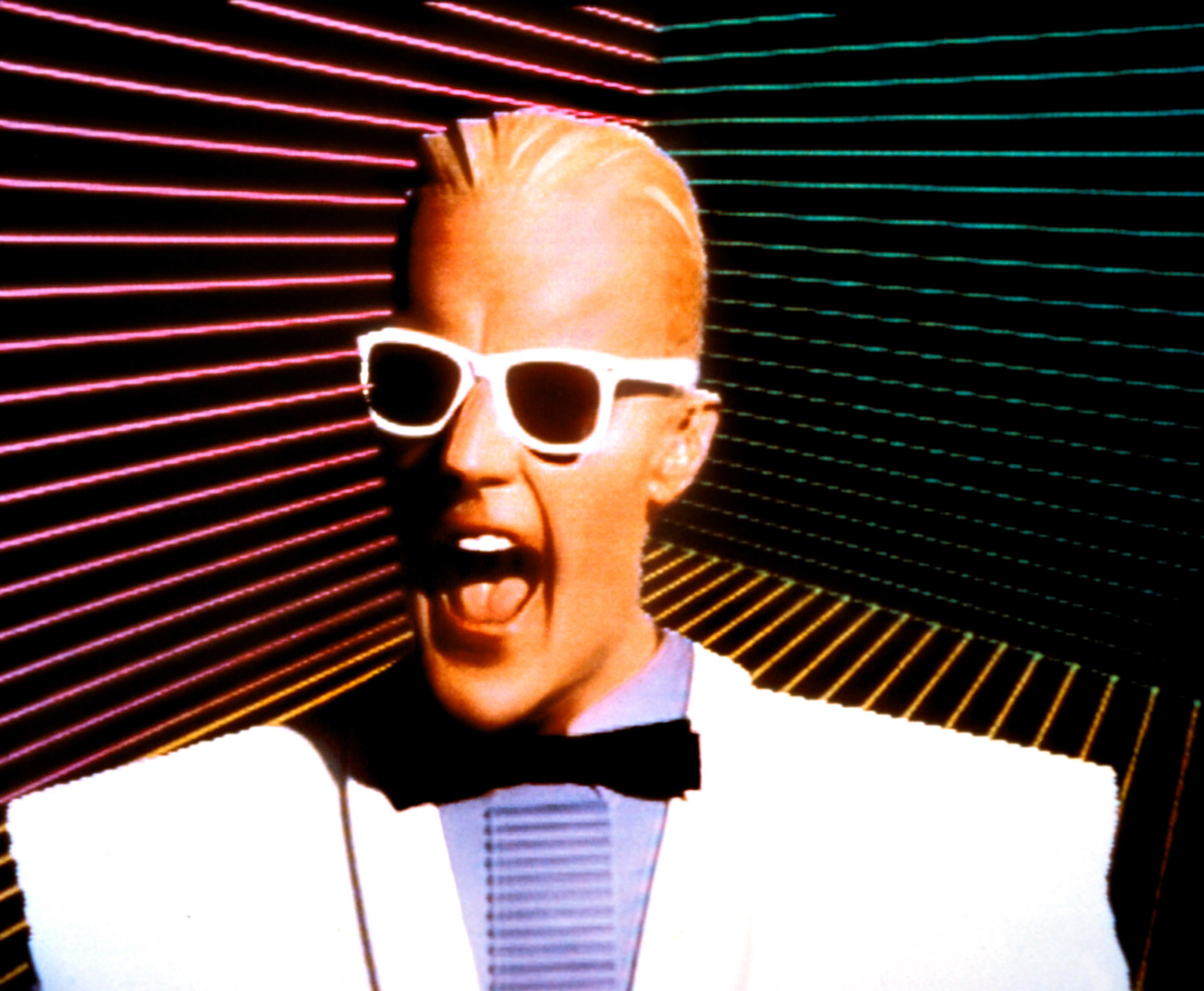 A promotional photo of Max Headroom wearing white Wayfarer sunglasses and a white suite with large shoulder pads