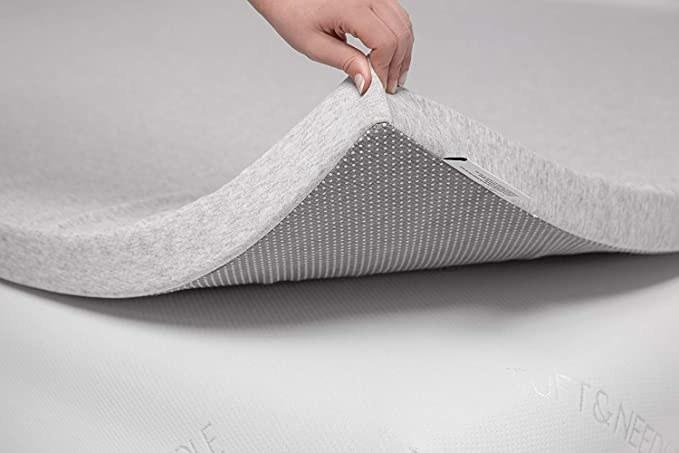 a hand lifting up the mattress topper