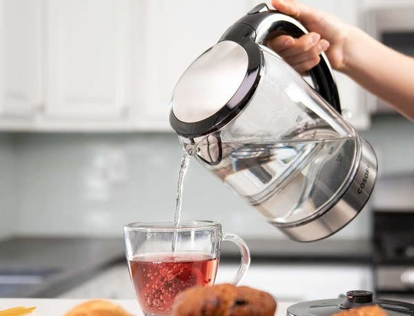 A person pouring boiling water from the kettle into a mug of tea