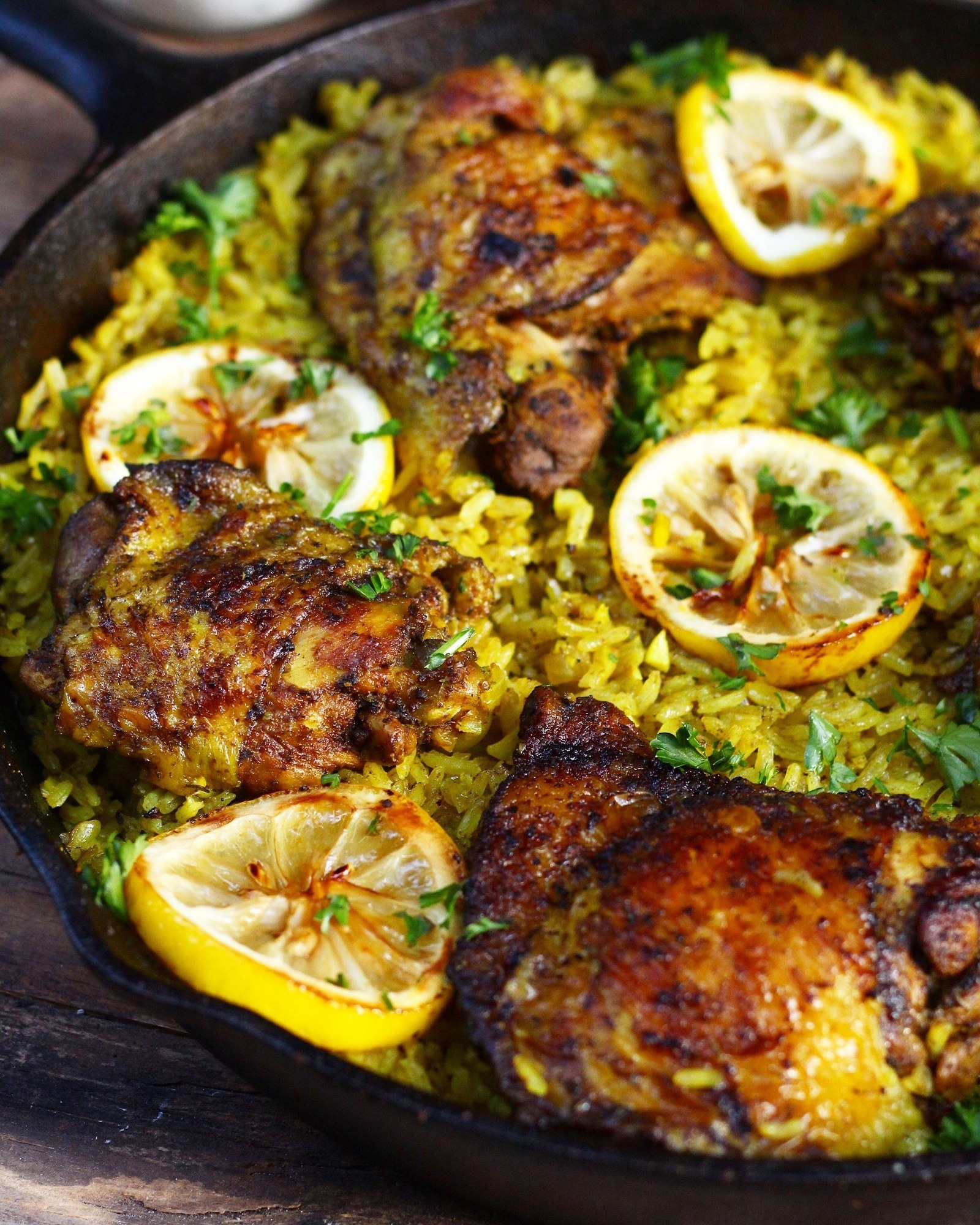 A cast iron skillet filled with chicken thighs over yellow rice with lemon wedges and herbs.