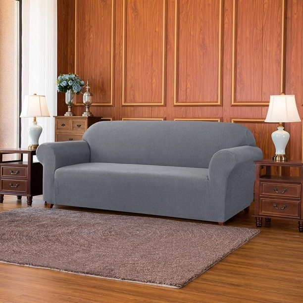 gray slipcover over a couch sitting in the middle of a room