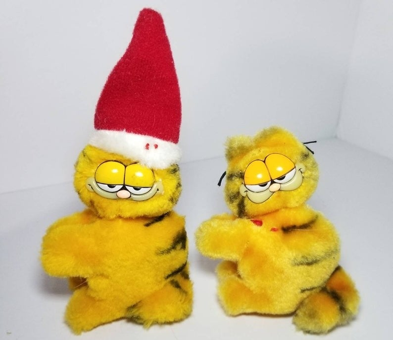 Two small Garfield hugger toys one wearing a Santa hat