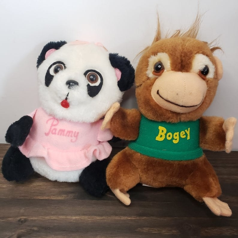 A stuffed animal of Pammy Panda in a pink dress and Bogey Orangutan in a green T-shirt