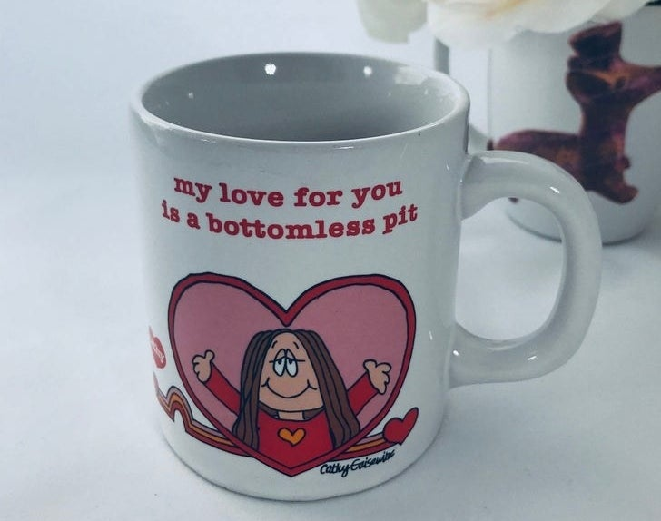 """A mug with Cathy in a heart reaching out for a hug with """"My love for you is a bottomless pit"""" written over her"""
