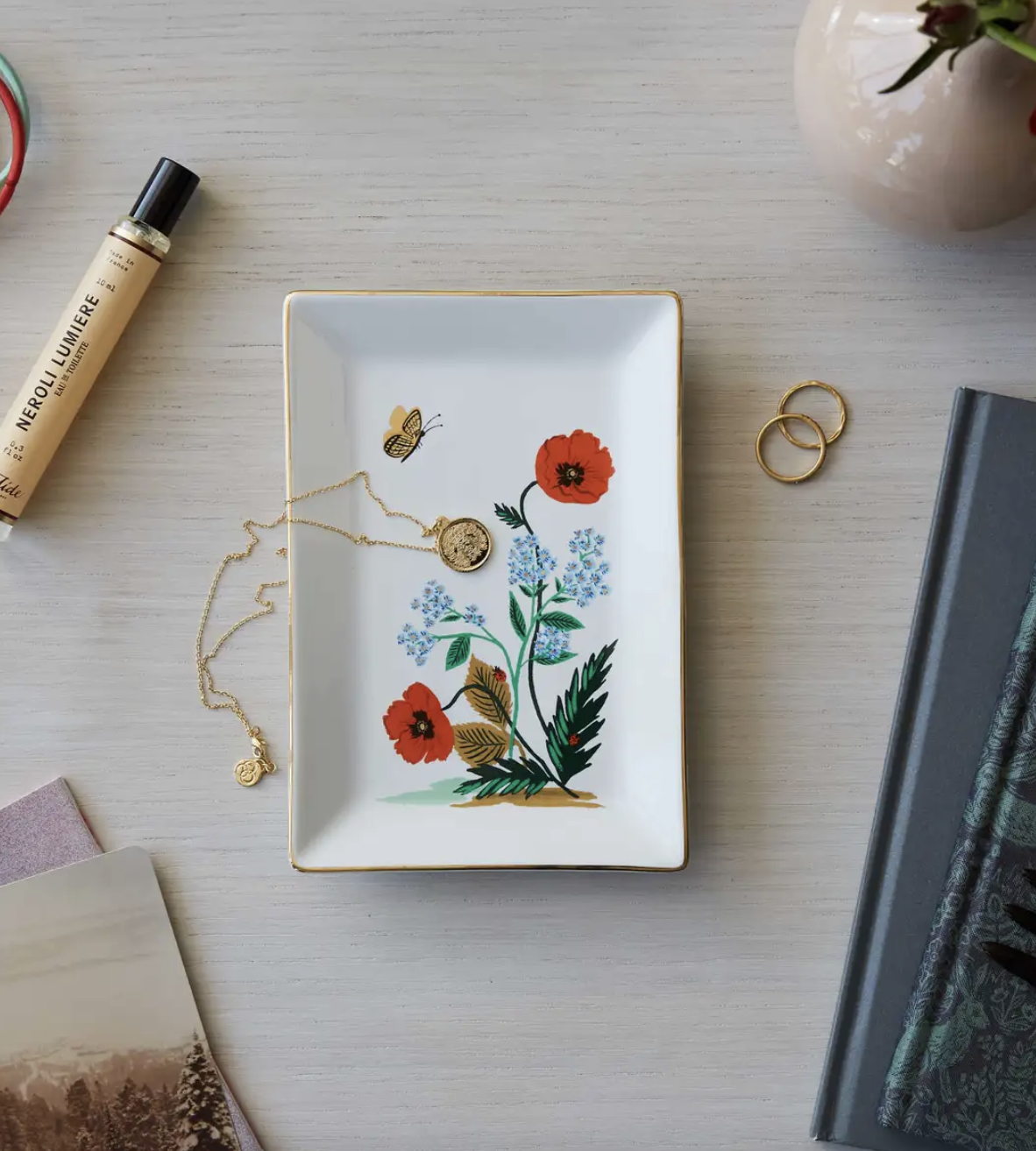 the tray, which has a floral design with a butterfly, holding a necklace