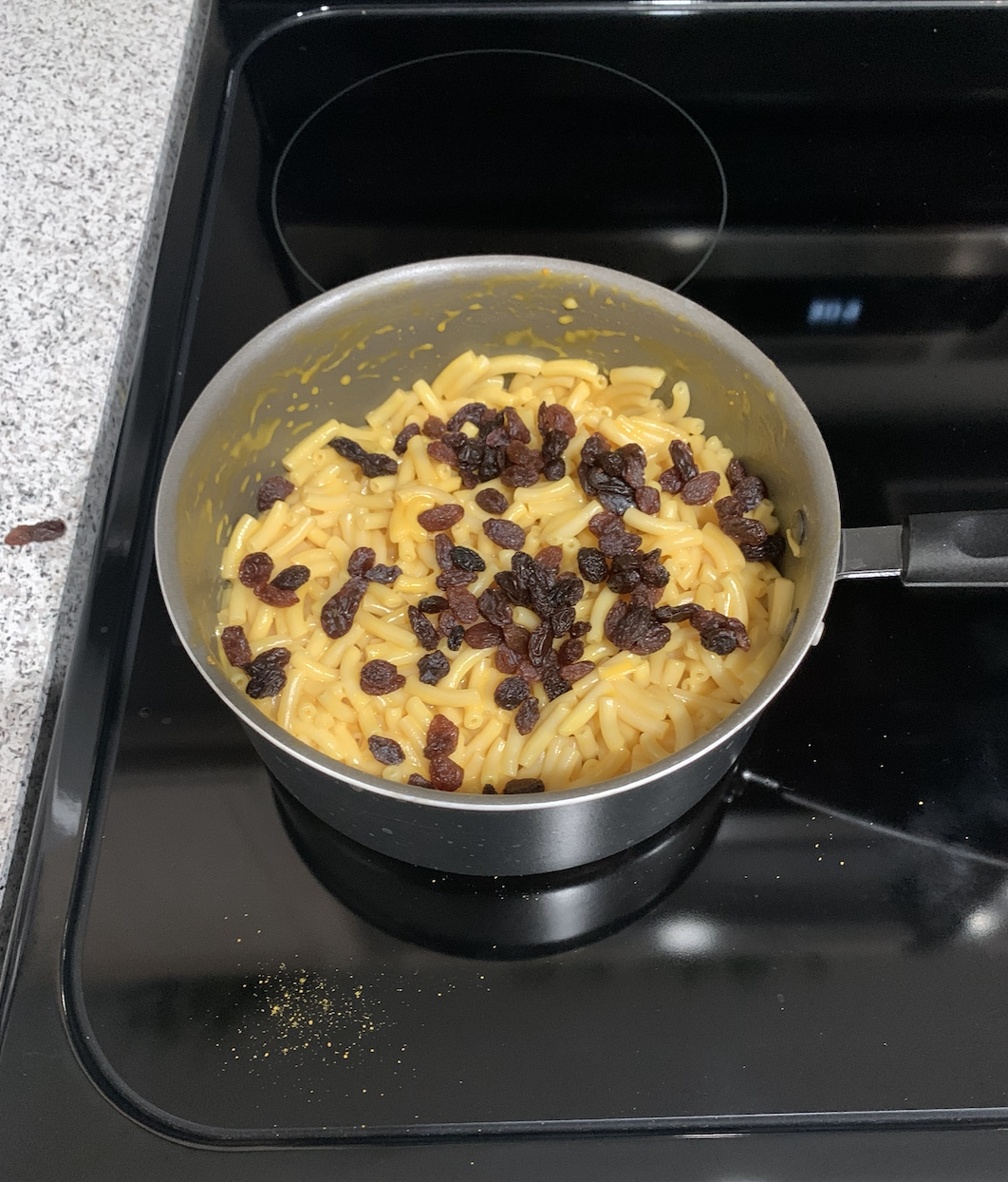 Questionable pot of macaroni and cheese topped with raisins