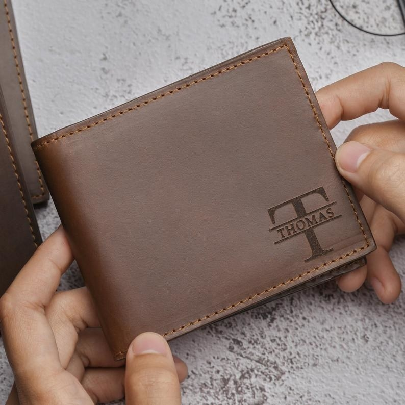 hands holding an engraved wallet