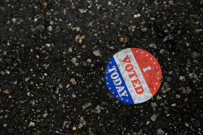 """An """"I Voted"""" sticker is stuck on the ground"""