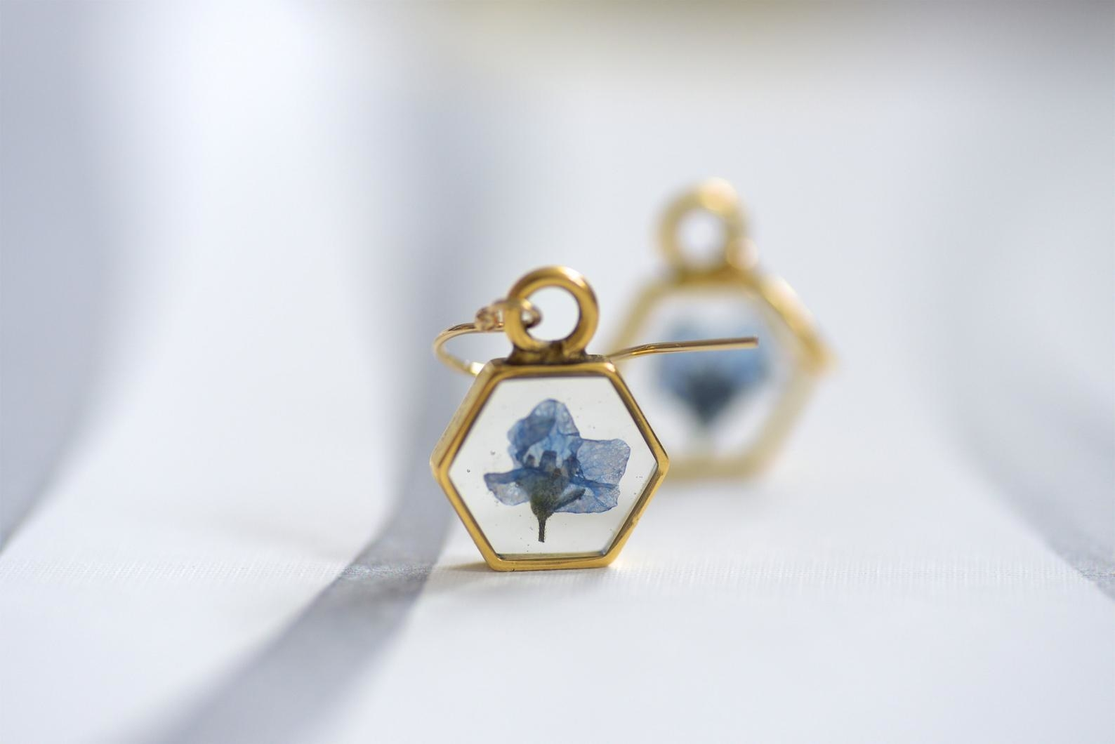 the hexagon earrings, which have a small pressed blue flower in the center