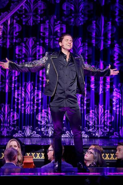 Aaron Tveit singing onstage