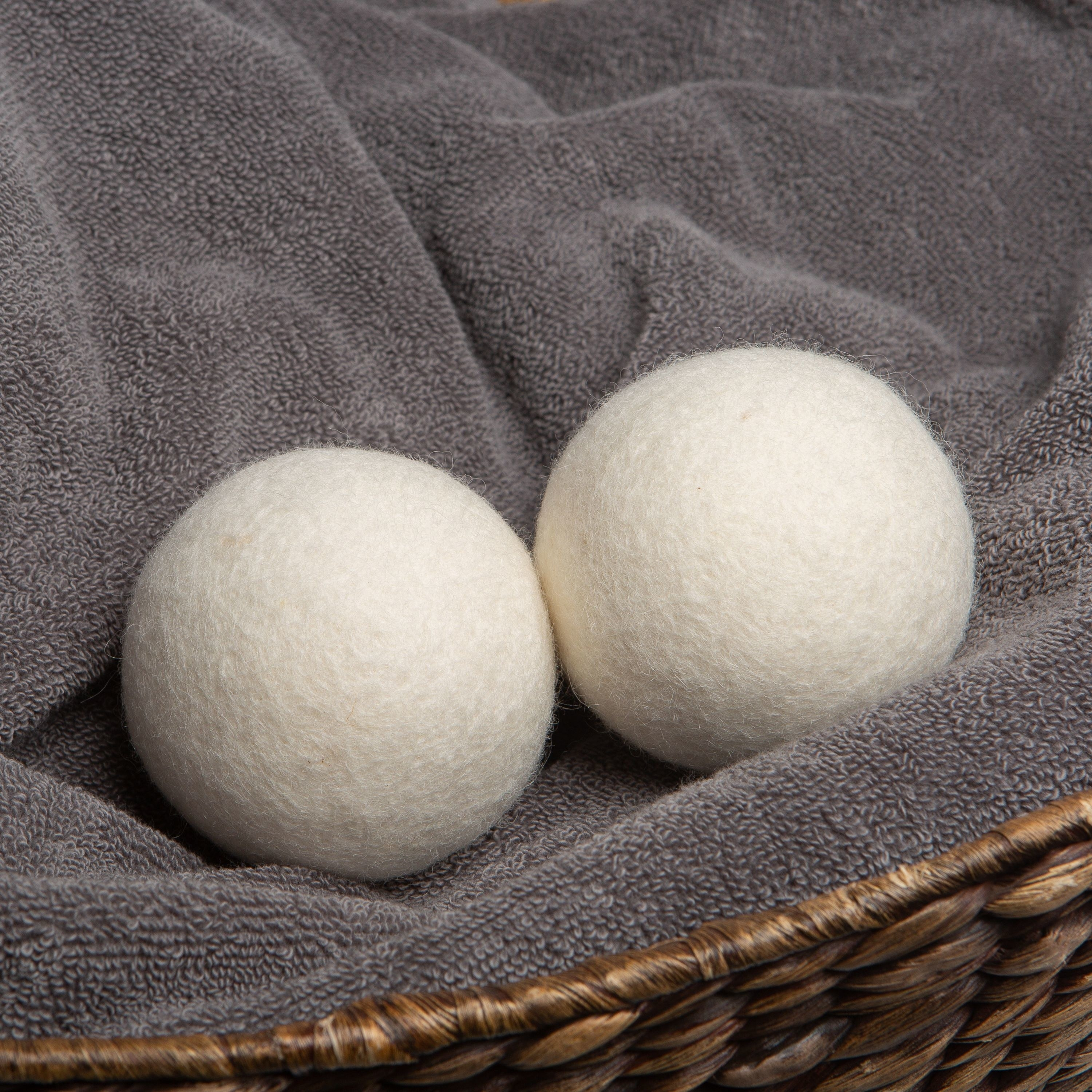 two wool dryer balls sitting in a laundry basket with a towel