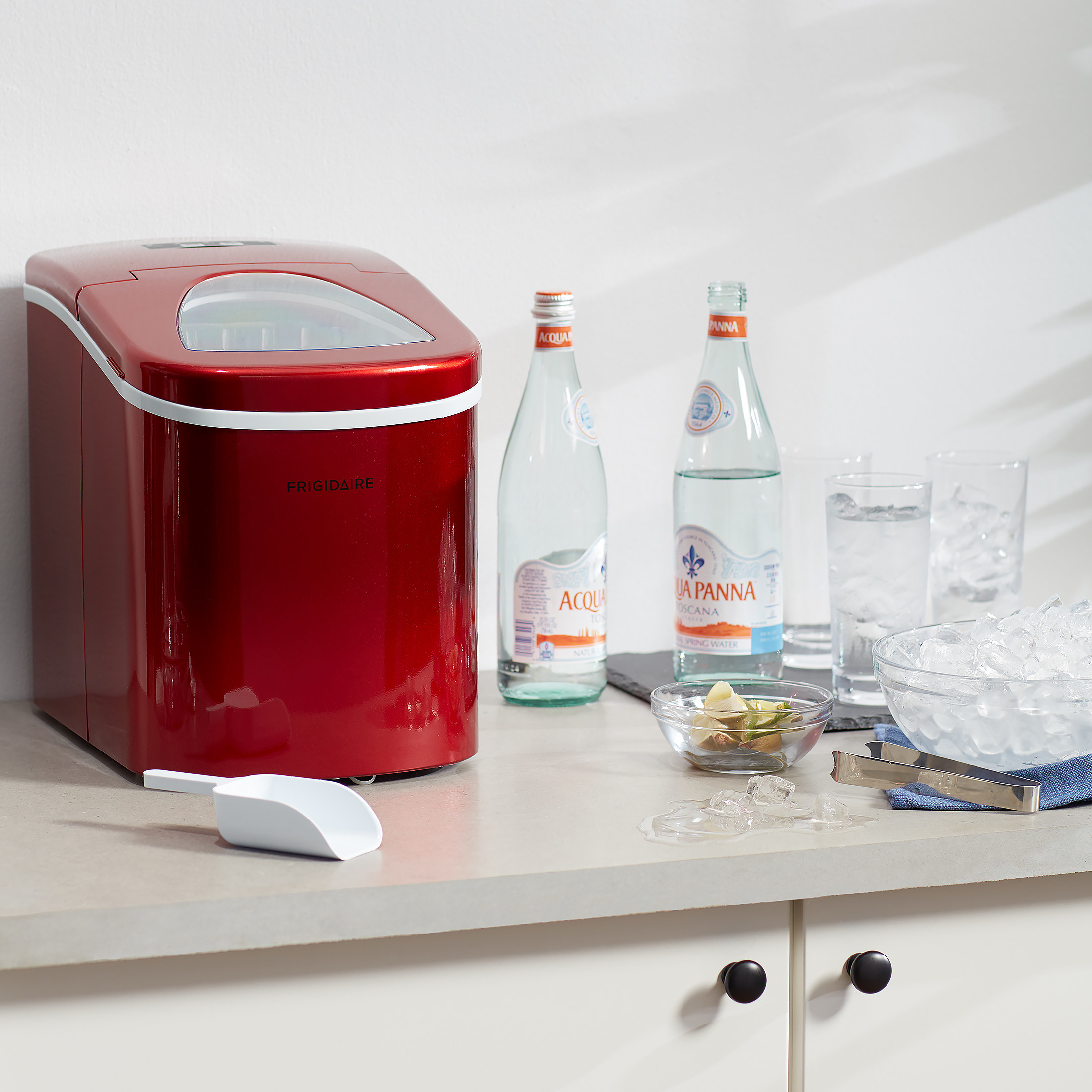 red icemaker on the counter next to bottles of water and glasses