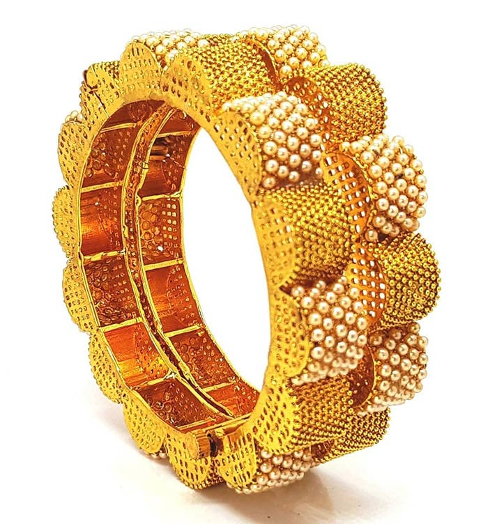 Two pairs of golden bangles with raised semic-circles, studded with pearls on the outside.