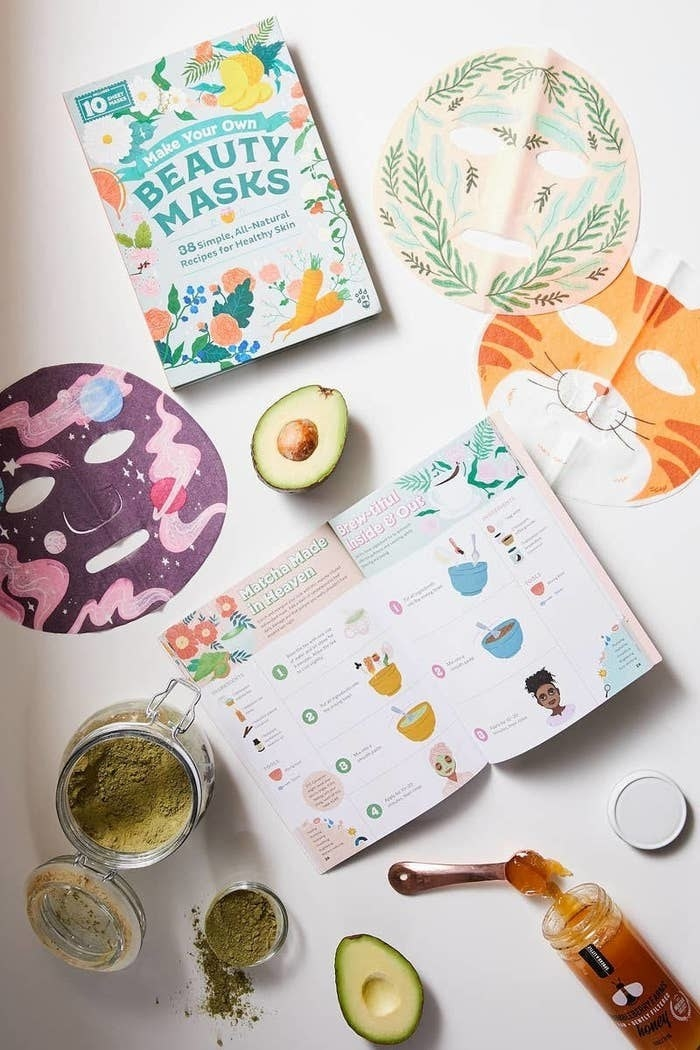 The book surrounded by various sheet mask ingredients and some of the sheet masks